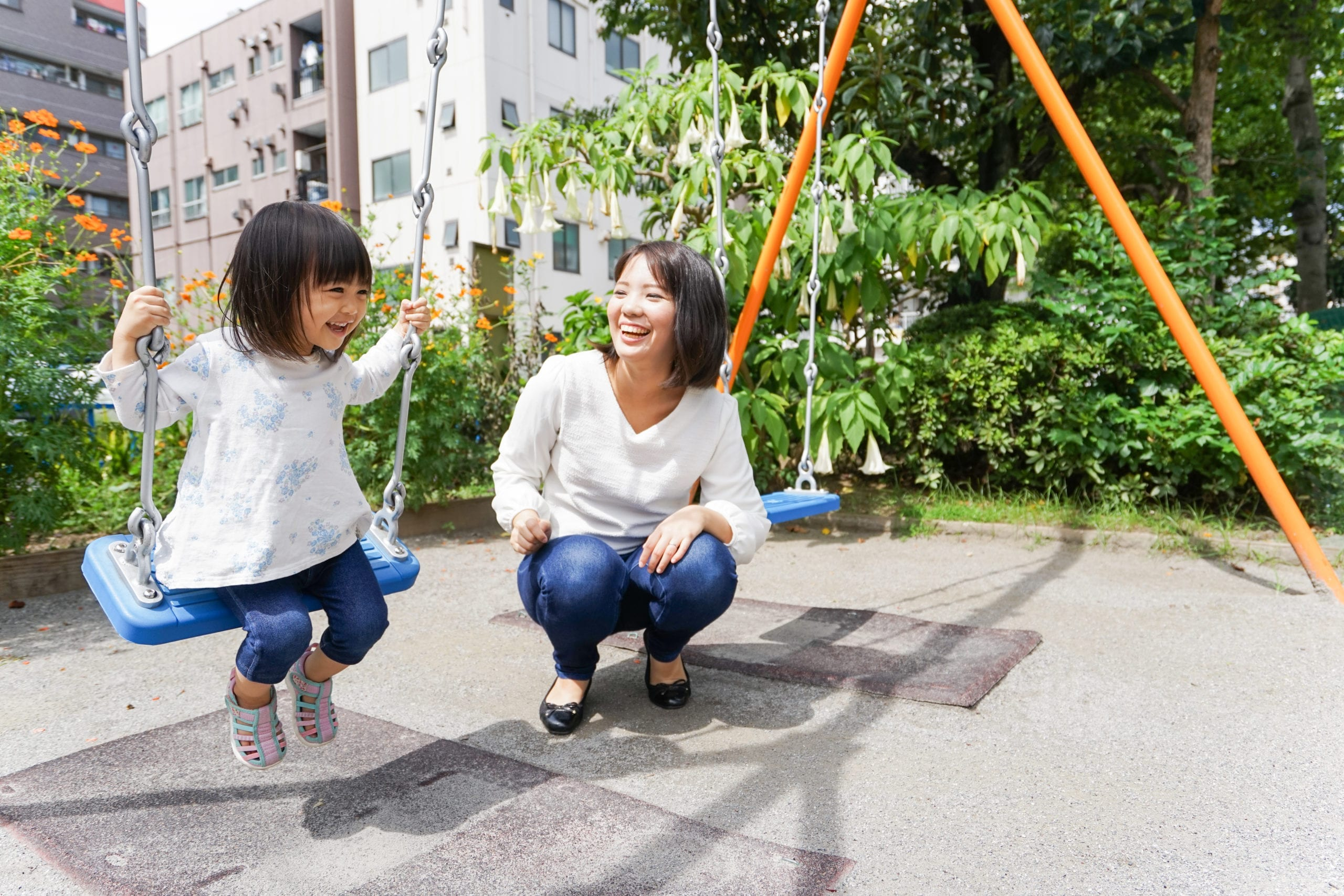 child playing outside on swing with mom